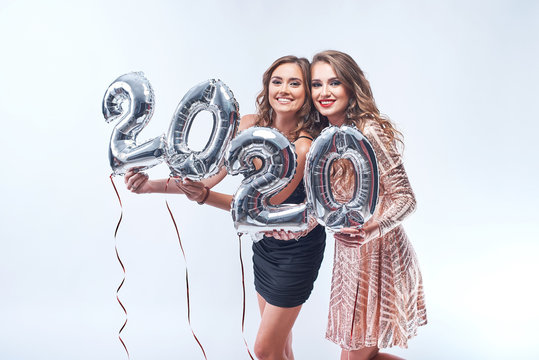 Happy young women in dresses with metallic foil 2020 balloons on white background.