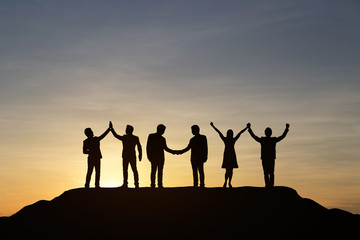 Silhouette of people are celebrating success at the top of the mountain, sky and sun light background. Team business concept.