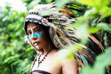 The beautiful woman wearing headdress feathers of birds. American Indian girl in native costume,posing in forest,blurry light around,art tone.