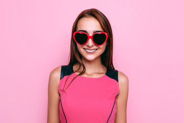 Stylish young woman in sunglasses posing on pink background