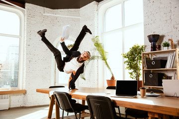 Young caucasian businessman having fun dancing break dance in the modern office at work time with gadgets. Management, freedom, professional occupation, alternative way of working. Loves his job. Papier Peint