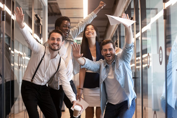 Portrait happy diverse employees celebrating business victory in hallway