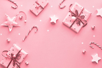 Festive monochrome pink Christmas background with pink gift boxes, stripy candy canes, trinkets and decorative stars, geometric flat lay with copy-space Fototapete