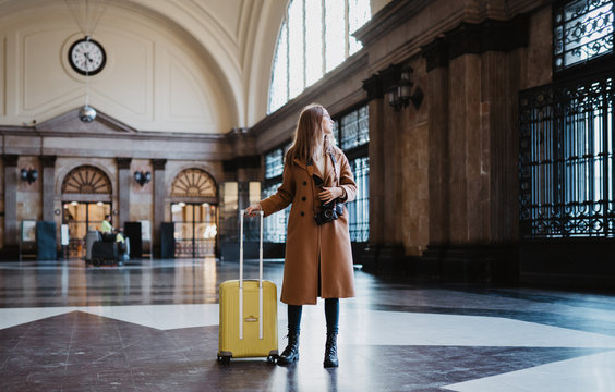 Tourist woman with suitcase on platform station in Barcelona. Girl traveler waiting train enjoy holiday weekend vacation in transport railway. Travel railroad station concept