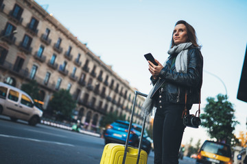 Traveler woman with suitcase calling mobile phone waiting yellow taxi in evening street europe city Barcelona. Girl tourist using smartphone wifi internet online gadget cellphone
