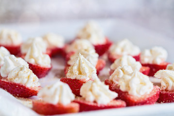 Stuffed strawberries filled with cheesecake filling made with whipped cream and cream cheese. Sprinkled with graham cracker crumbs. Selective focus with blurred foreground and background.