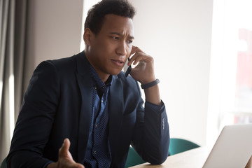 Angry black businessman disputing on phone at office