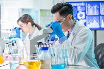 Asian scientist use microscope