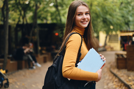 Pretty smiling casual student girl with books happily looking in camera in park