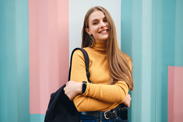 Beautiful smiling casual student girl joyfully looking in camera over colorful background