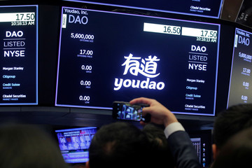 Man takes picture of a screen during Youdao Inc. IPO at the New York Stock Exchange (NYSE) in New York