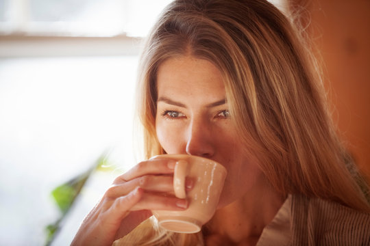 Close-up of woman having drink while standing against window in kitchen at home