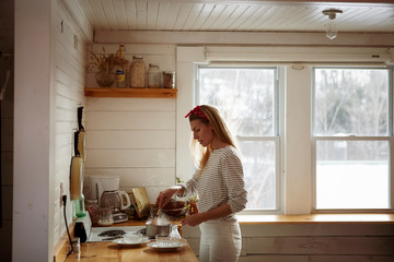 Side view of woman cooking food in kitchen