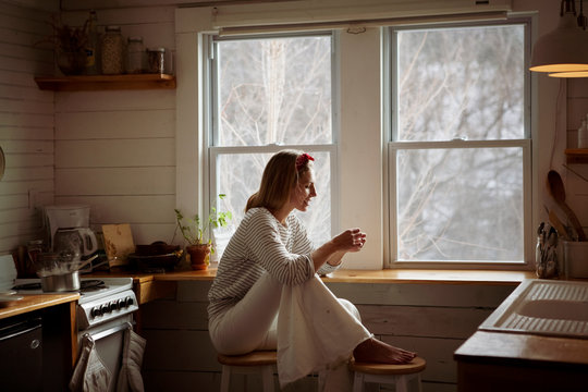 Side view of woman sitting on stools against window at home