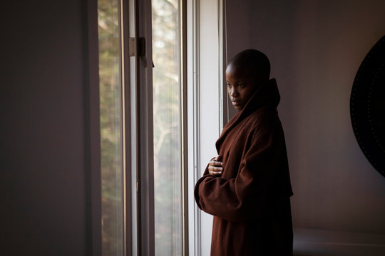 Side view of thoughtful woman wearing bathrobe looking through window while standing at home
