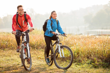 Fototapeta Beautiful happy young couple enjoying early morning bicycle ride by the river or lake. Sunrise through the mist above water in the background obraz