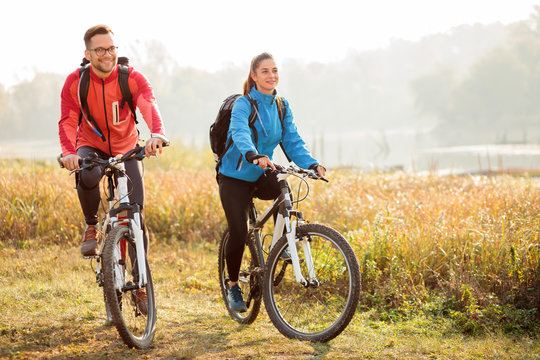 Beautiful happy young couple enjoying early morning bicycle ride by the river or lake. Sunrise through the mist above water in the background
