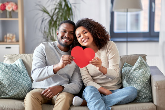 love, valentines day and relationships concept - happy african american couple holding red heart together at home