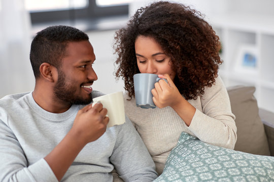 leisure and people concept - happy african american couple drinking coffee or tea at home