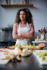 Thoughtful female chef with food on table standing against wall in kitchen