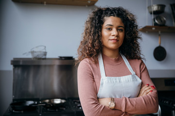 Portrait of confident female chef with arms crossed standing against wall in kitchen