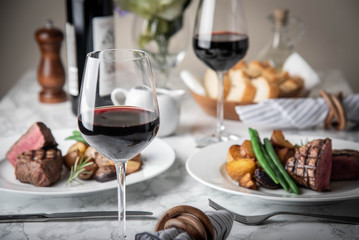 wine glasses on dining table with steak