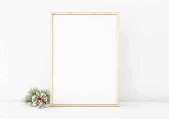 Vertical christmas poster mockup with golden frame and pine cone on white wall background. 3D rendering, illustration.