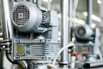 blurred industrial background with electric motor on the foreground