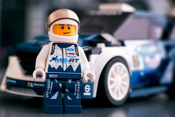 Tambov, Russian Federation - October 18, 2019 Lego Ford Fiesta M-Sport WRC driver minifigure by LEGO Speed Champions and his car on background. Studio shot.