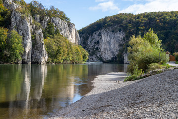 Passenger ship passing Danube breakthrough near Kelheim, Bavaria, Germany in autumn with gravel bank in foreground and limestone formations in the background