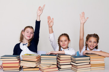 three girls raise their hand up in school class