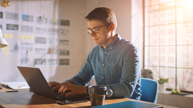 Professional Creative Man Sitting at His Desk in Home Office Studio Working on a Laptop. Man working with Data and Analyzing Statistics.