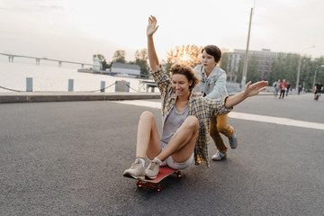 Cheerful son riding his mother on a skateboard and laughing. Single mother spending time with her son outdoors