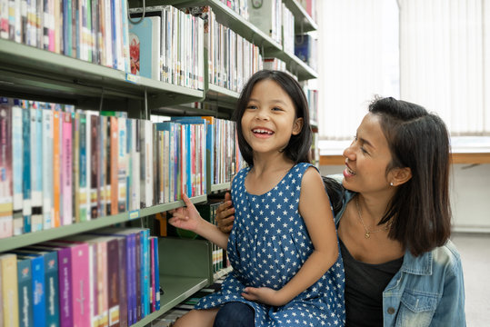 Asia mother and daughter picking a book in public library