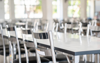 Stainless steel tables and chairs in high school student canteen, public cafeteria room interior background