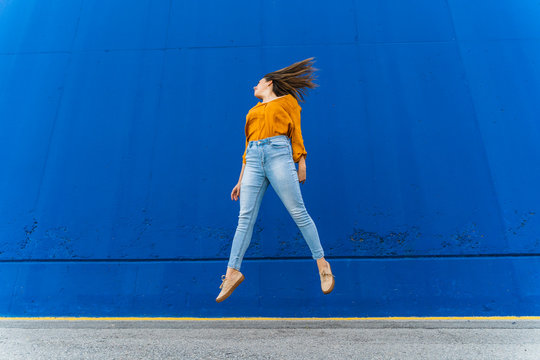 Young woman jumping against blue wall