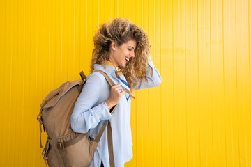 Laughing young woman carrying backpack in front of yellow background