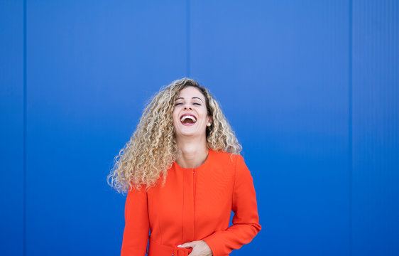 Portrait of laughing young woman wearing red dress in front of blue background