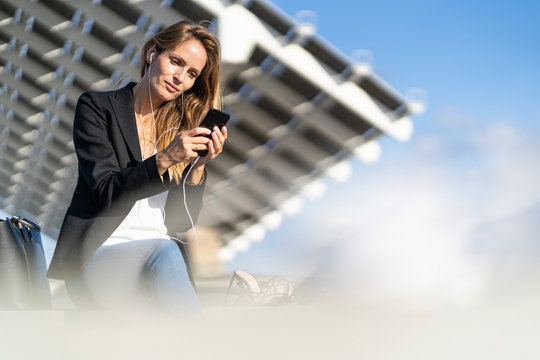 Businesswoman sitting on a wall with smartphone and earphones