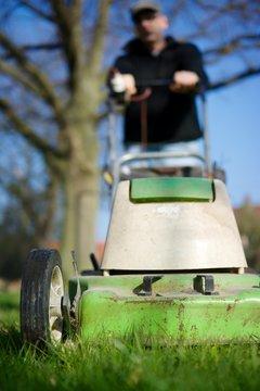 Germany, Petershagen, Man mowing lawn