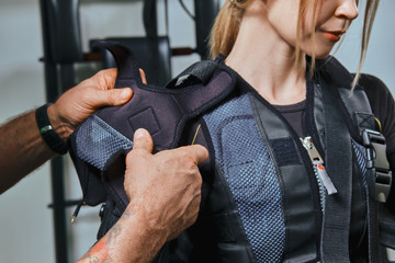 Muscular fitness instructor is putting on an ems suit for athletic woman. Training in a gym by a method to increase energy.