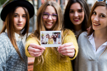 Four young women showing their instant photo