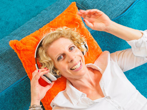 Portrait of smiling blond woman listening music with headphones