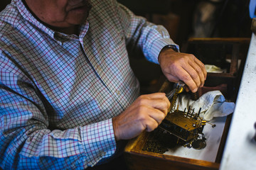 Watchmaker hands in the foreground working with an antique clock