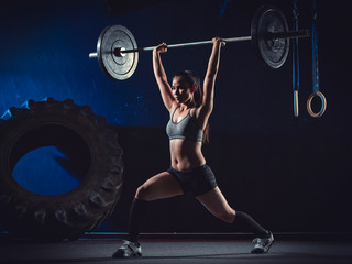 CrossFit athlete at weight training looking with barbell