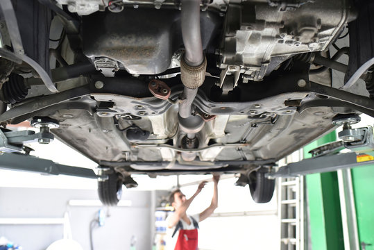 Car mechanic working in repair garage, checking underbody of a car