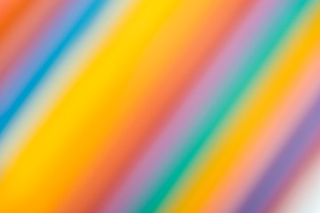 blurred background of rainbow colors of different colors laid out by pencils