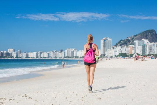 Brazil, Rio de Janeiro, back view of woman jogging on the beach