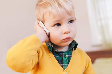 Portrait of serious looking toddler telephoning with smartphone