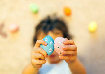 Girl's hands holding two painted Easter eggs